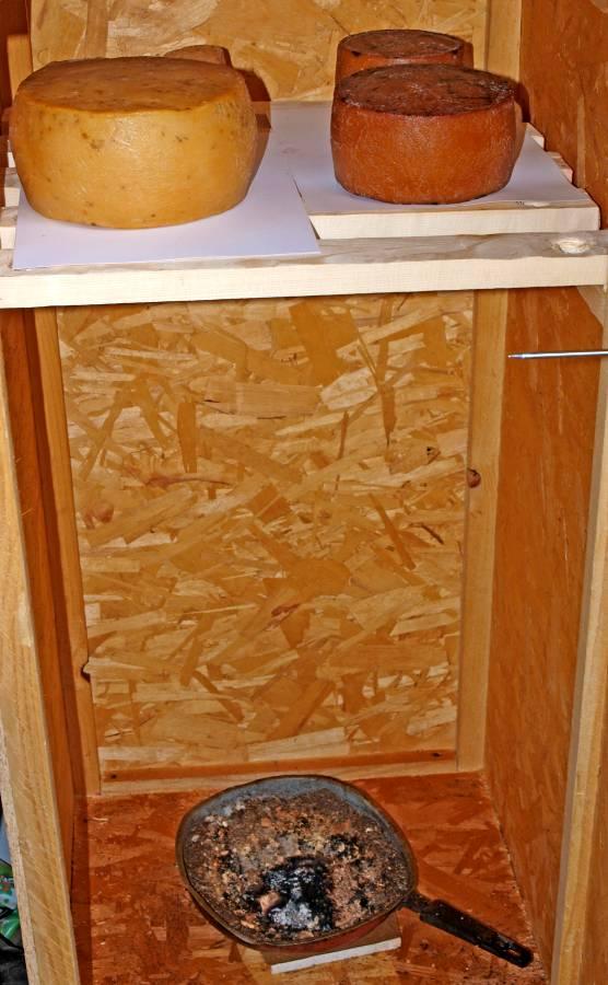 Ein Räucherschrank aus Holz der mit Käse gefüllt ist.